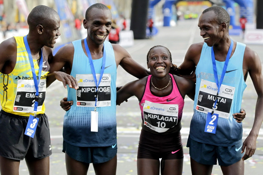 Kenijka Florence Kiplagat świętuje z kolegami zwycięstwo w półmaratonie w Barcelonie i nowy rekord świata kobiet. Fot. PAP