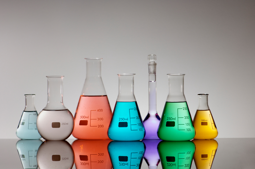 group of seven flasks containing different kinds of brightly colored liquid