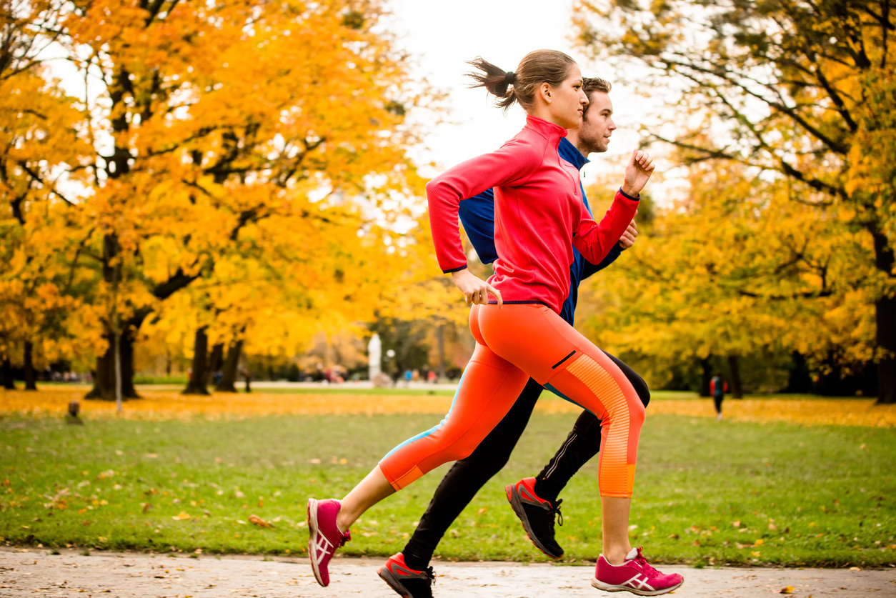 Young couple jogging together in park - rear view