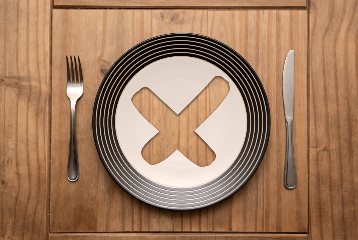 Cross mark on plate with fork and knife on rustic wooden table in natural light, top view